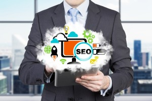 Businessman is holding a tablet with cloud projection and the acronym 'SEO'